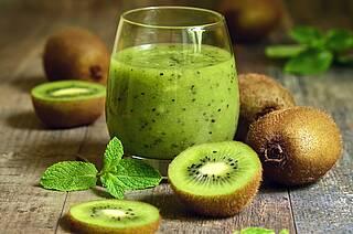 Kiwi-Früchte ganz, aufgeschnitten, als Smoothie püriert.