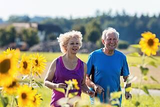 Zwei junge Senioren joggen am Sonnenblumenfeld.