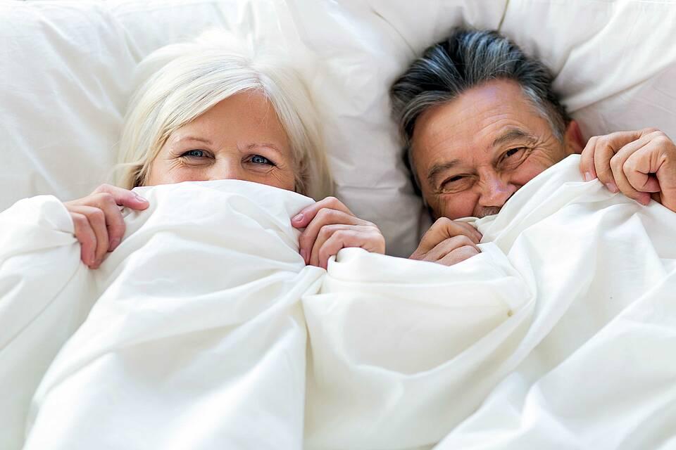 Älteres Paar schaut vergnügt unter weißer Bettdecke hervor.