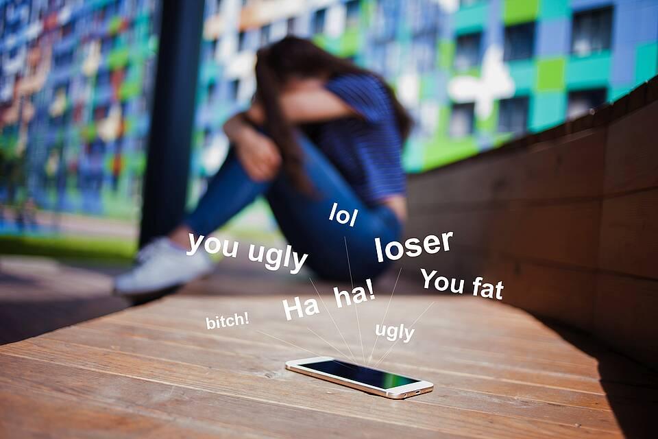 Mädchen sitzt geknickt vorm Handy - umschwirrt von Schimpfwörtern wie Loser, Bitsch, ugly ...