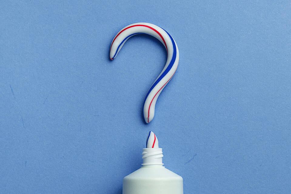 Zahnpasta-Tube mit ausgedrückter Zahnpasta in Form eines Fragezeichens.