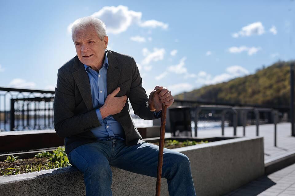 Alter Mann muss beim Spazierengehen pausieren und sich hinsetzen wegen Herzschwäche.
