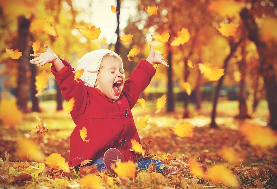 Kind wirbelt goldenes Herbstlaub auf.