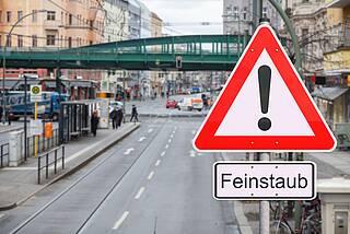 """Warnschild """"Feinstaub"""" an einer Straße in Berlin."""