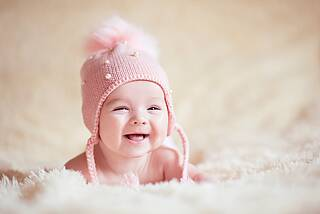 Mädchen im Säuglingsalter mit rosa Häkelmütze.
