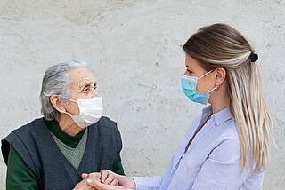 Alte und junge Frau mit grünen Corona-Masken