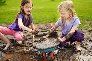 Mädchen spielen mit brauner Matsche in der Pfütze