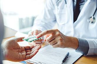 Arzt überreicht Patient Blister mit weißen Tabletten