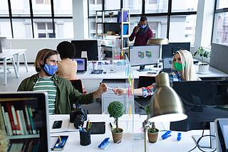 Lustige Büroatmosphäre mit Coronamasken.