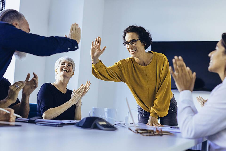 Arbeitskollegen klatschen sich die Hände ab, um einen Erfolg zu feiern.