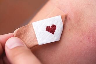 Pflaster an Einstichstelle einer Spritze am Arm: Blutstropfen auf Pflaster hat Herz-Form.