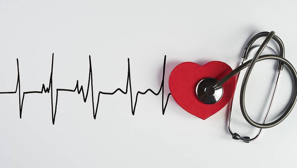 Herzrhythmusstörungen - Symbolbild mit EKG-Kurve, rotem Herz aus Moosgummi und Stethoskop.