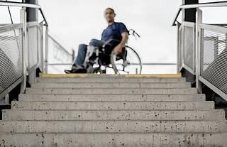 Behinderter im Rollstuhl vor unpassierbarer Steintreppe