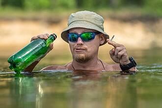 Mann beim Baden mit grüner Schnapsflasche, hellem Sonnenhut  und Kipper