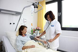 Patientin im Krankenhaus kriegt Blutdruck gemessen.