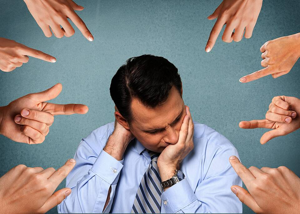 Mann in Grübler-Pose - acht Finger zeigen auf ihn.