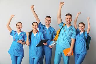 Fünf Studenten, männlich/weiblich, in blauen Kitteln, mit Blocks, Taschen, Büchern