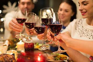 Runde eleganter Leute prostet sich mit gut gefüllten Rotweingläsern zu