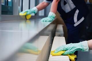 Putzende Hände in grünen Gummihandschuhen mit gelben Putzlappen.