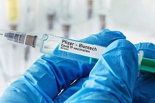 """Hand mit blauem Gummihandschuh hält COVID-19 Impfstoffspritze mit Etikett """"Pfizer-Biontech"""""""""""