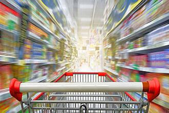 Einkaufswagen Supermarkt, Griffleiste mit Regalen im Hintergrund