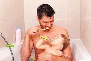 Kind und Papa putzen Zähne in der Badewanne.