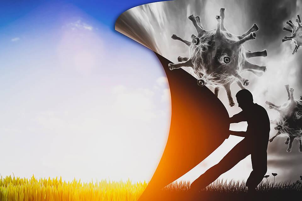 Mann inmitten von grauen Corona-Viren zieht mit Kraft eine Wand auf - und die Sonne kommt.