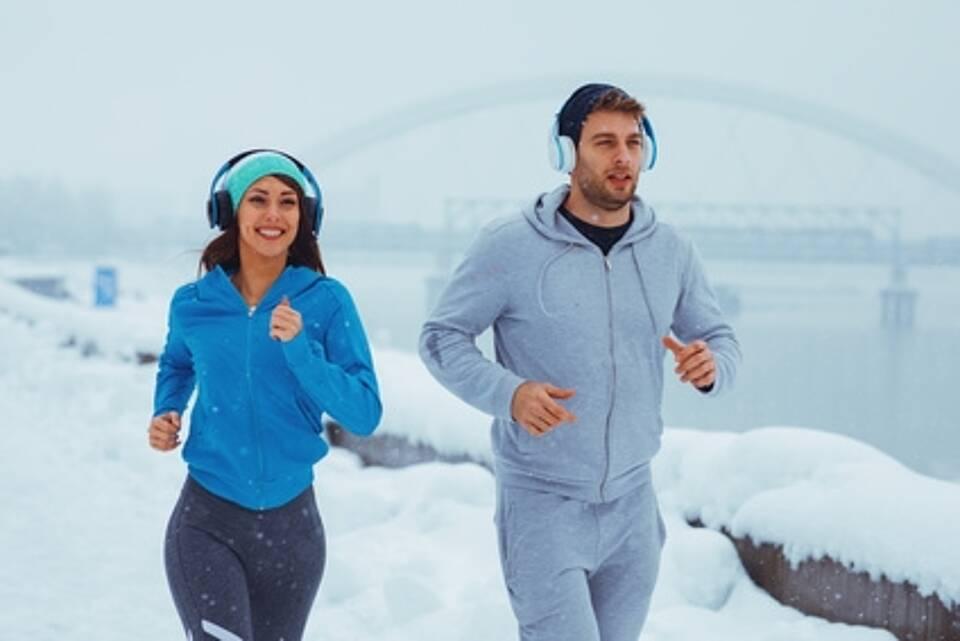 Mann und Frau Joggen bei Schnee am Fluss entlang