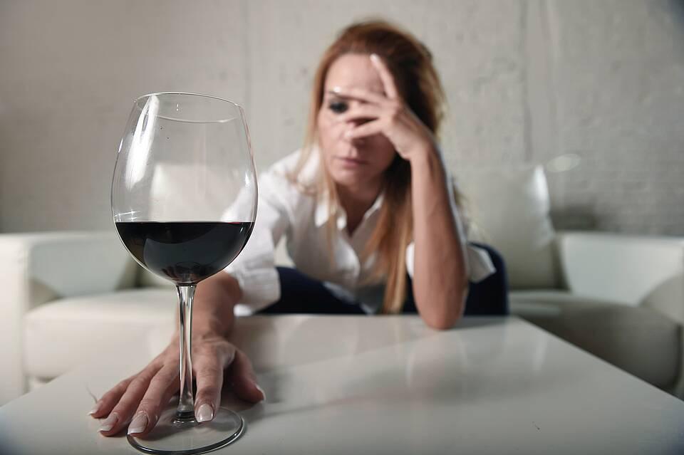Frau vor Rotweinglas - stützt sich grüblerisch mit der Hand den Kopf ab.