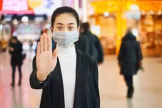 Nicht näherkommen: Frau mit Mundschutz - Stop-Signal mit  ausgestreckter Hand