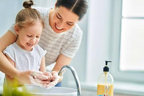 Mutter bringt kleinem Mädchen das Händewaschen bei.