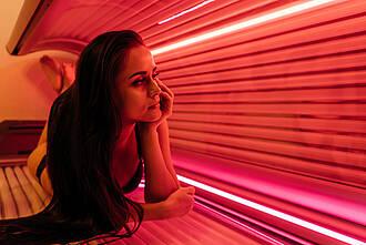 Frau liegt im Solarium