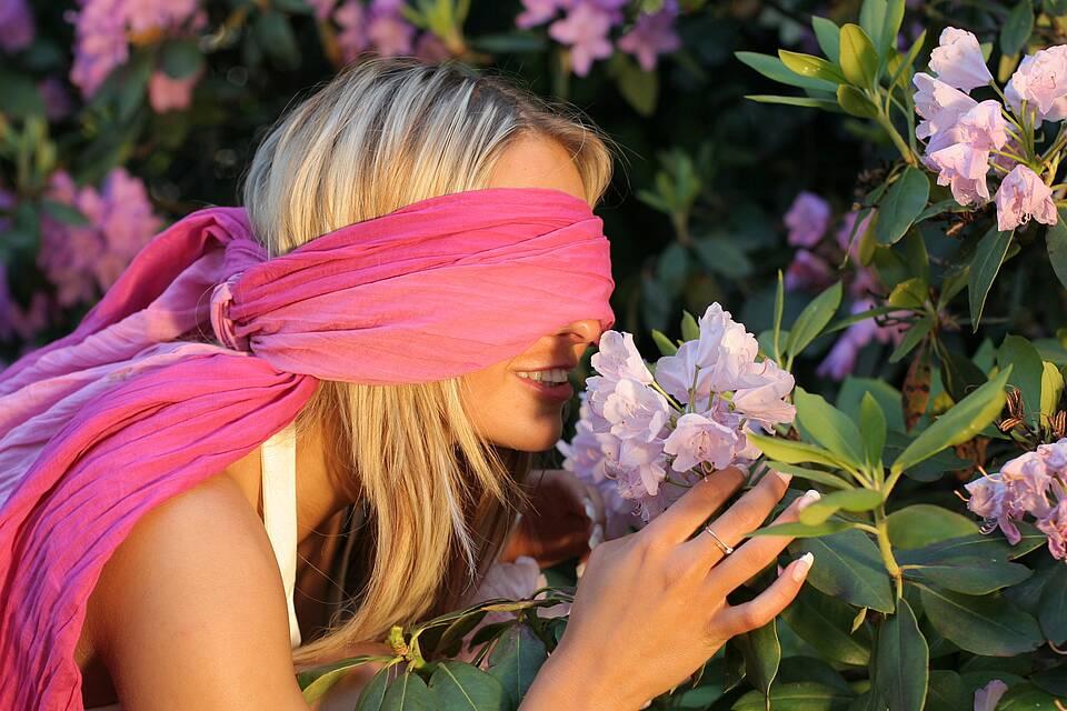 Frau riecht mit verbundenen Augen an einer Blüte.