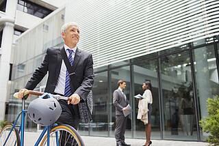 Mann im Business-Anzug fährt mit dem Fahrrad ins Büro.