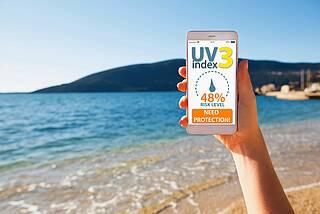 Smartphone zeigt am Strand einen UV-Index-Wert von 3 an.