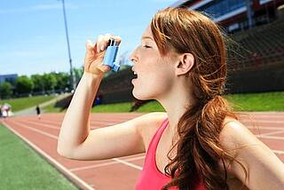 Sportlerin mit Asthmaspray vor roter Aschenbahn im Stadion