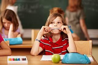 Junge sitzt im Klassenzimmer und knabbert an einem Bleistift.
