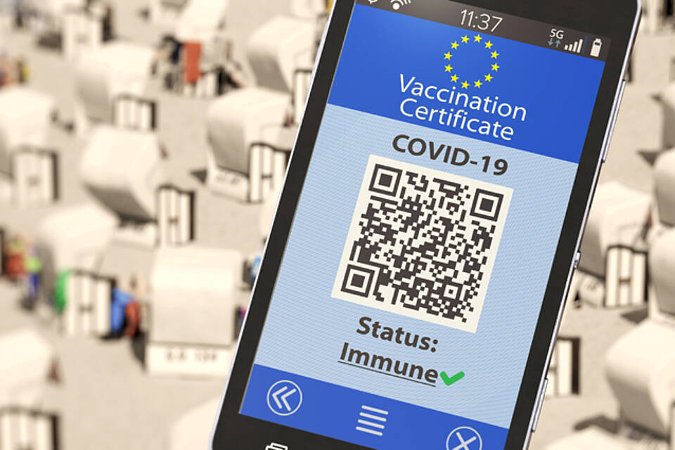 Digitaler Immunitätsnachweis auf dem Smartphone - im Hintergrund: Strandkörbe.