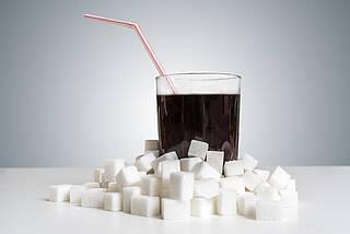 Glas mit Cola, drumherum Zuckerwürfel.