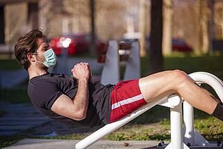 Corona: Mann macht Fitness im Park