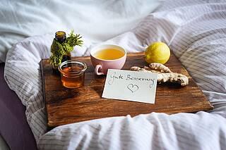 Tee, Ingwer, Zitrone - auf Tablett im Bett.