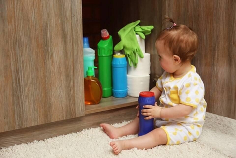 Kleinkind spielt mit Putzmitteln