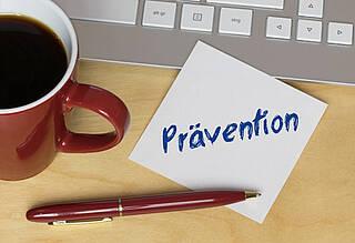 "Kaffeetasse, PC-Tastatur, Stift, Zettel mit Vermerk ""Prävention"""