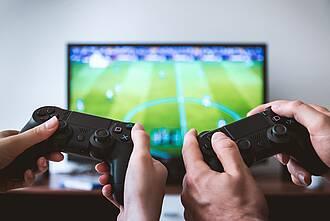 Zwei Joysticks im Vordergrund mit Händen am Drücker, Monitor mit Fußball-Computerspiel im Hintergrund