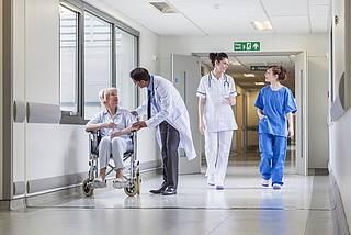 Patientin im Rollstuhl auf dem Krankenhausgang mit Ärzten und Pflegepersonal.