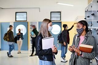 Studenten mit Corona-Masken unterhalten sich.
