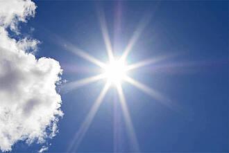 Sonne strahlt weiß am blauen Himmel