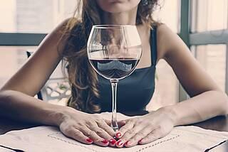 Frau vor Rotweinglas.