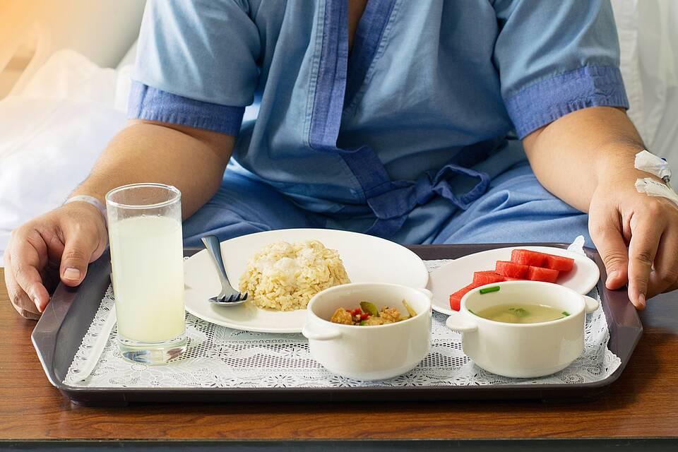 Krankenhaus: Patient sitzt vor Tablett mit Essen