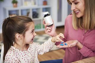 Mutter gibt Kind blaue Arzneikapseln auf die Hand